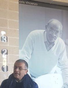 Saverio Calia con alle spalle la gigantografia del padre, fondatore dell'azienda, posta nella hall dello stabilimento principale a Matera